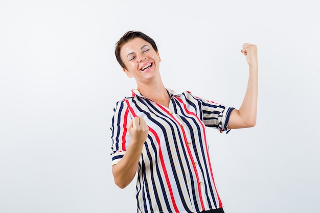 Donna matura che mostra il gesto del vincitore in camicetta a righe e sembra fortunato. vista frontale.