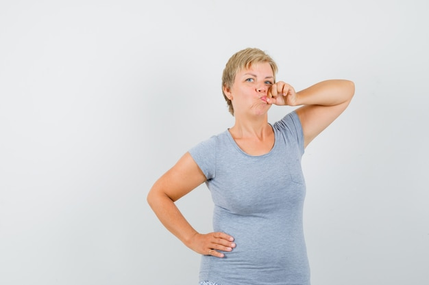 Mature woman showing zip gesture in grey t-shirt and looking serious