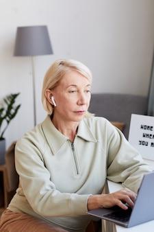 テーブルに座って自宅のコンピューターで入力する成熟した女性彼女は彼女のオンライン作業に集中しています