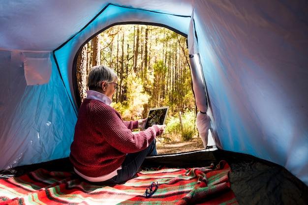 無料の野生のキャンプでテントの中に座っている成熟した女性