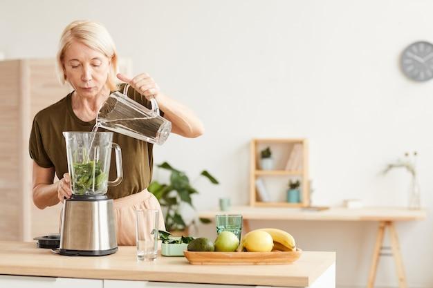 ダイエット中の成熟した女性と彼女は彼女のキッチンで朝に健康的なカクテルを準備しています
