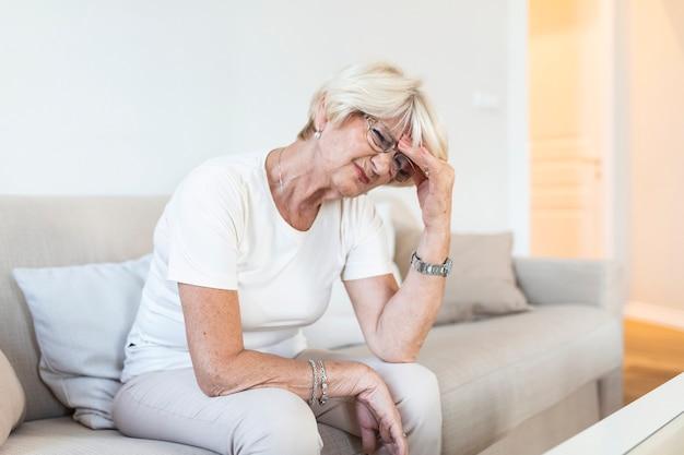 Зрелая женщина, сидящая на белом диване в доме, касаясь своей головы рукой, испытывая головную боль и плохо себя чувствуя