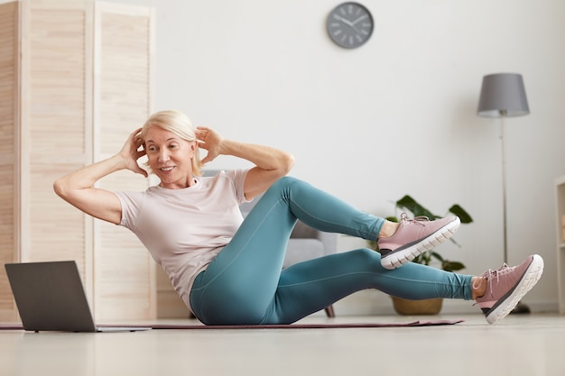 エクササイズマットに座って、自宅で座っている間、ラップトップでオンラインでスポーツトレーニングを見ているエクササイズをしている成熟した女性