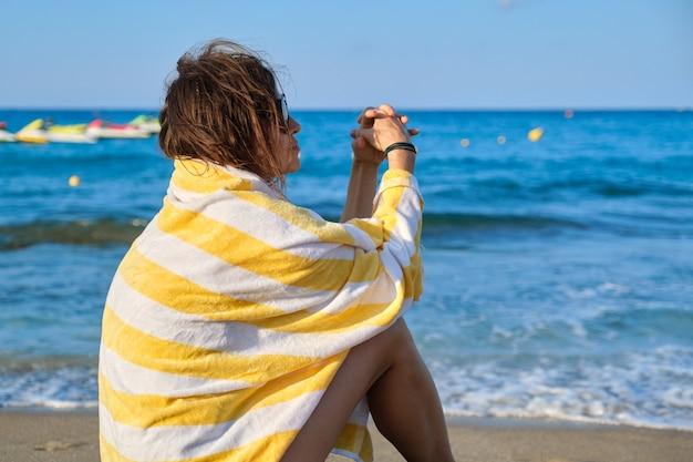 彼女の肩にビーチタオルで美しい女性を休んで海岸に座っている成熟した女性。美しい夕日の風光明媚な海の背景。リラックス、レジャー、美容、海、中年のライフスタイル