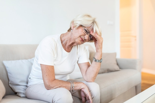 Mature woman sitting on a white sofa in a home touching her head with her hand while having a headache pain and feeling unwell