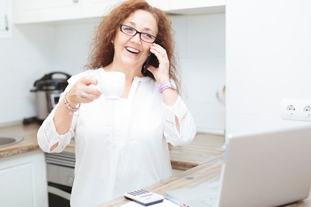 Mature woman smiling on the phone while holding a cup of coffee.