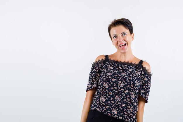 Зрелая женщина улыбается, позирует в блузке и выглядит счастливой. передний план.