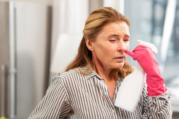 アレルギーを持っている間掃除のために化学薬品を使用した後くしゃみをする成熟した女性