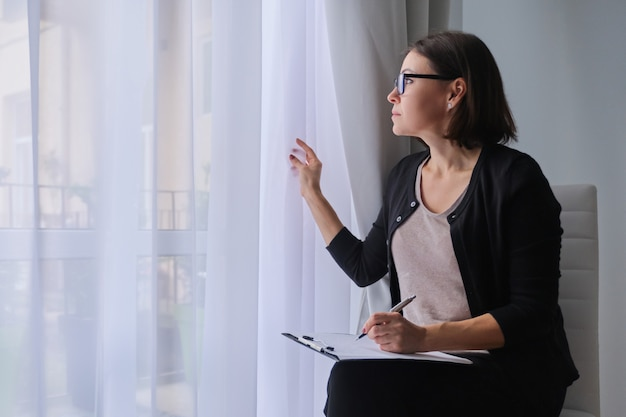 Mature woman social worker, psychologist sitting near the window with clipboard