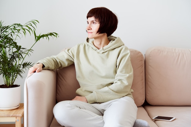 Mature woman spending time at home sitting in room on couch and looking sad digital detox concept