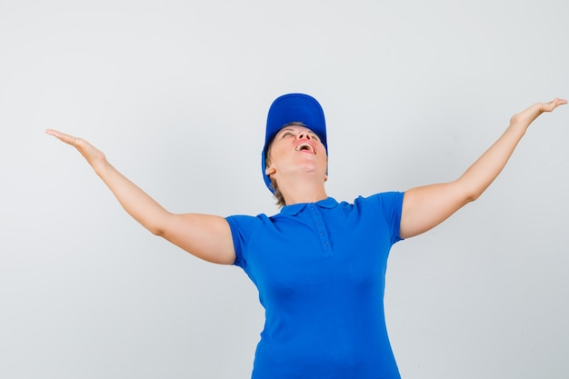 Mature woman spreading arms while looking up in blue t-shirt and looking blissful.