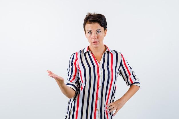 手のひらを脇に広げ、縞模様のブラウスで腰に手をつないで、真剣に見える成熟した女性、正面図。