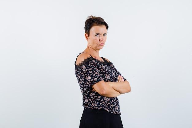 Donna matura in piedi con le braccia incrociate in camicetta floreale e gonna nera e guardando fiducioso, vista frontale.