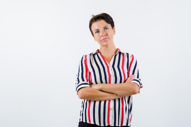 腕を組んで縞模様のシャツを着て、自信を持って見える成熟した女性。正面図。