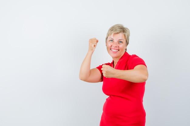 Зрелая женщина, стоящая в позе боя в красной футболке и уверенно выглядящая