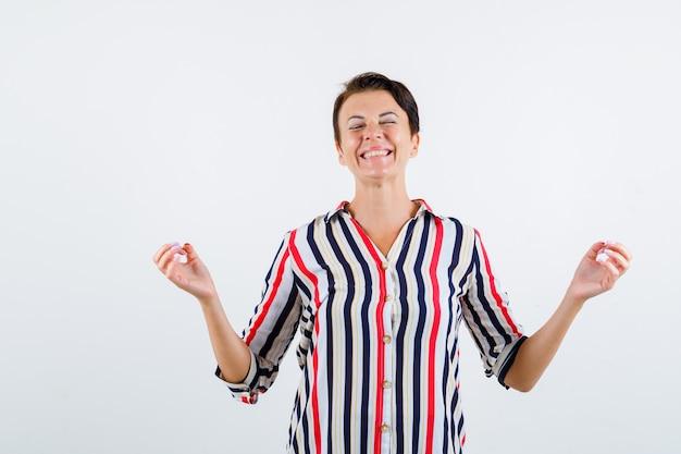 Зрелая женщина, стоя в позе медитации, закрывая глаза в полосатой блузке и выглядела счастливой. передний план.