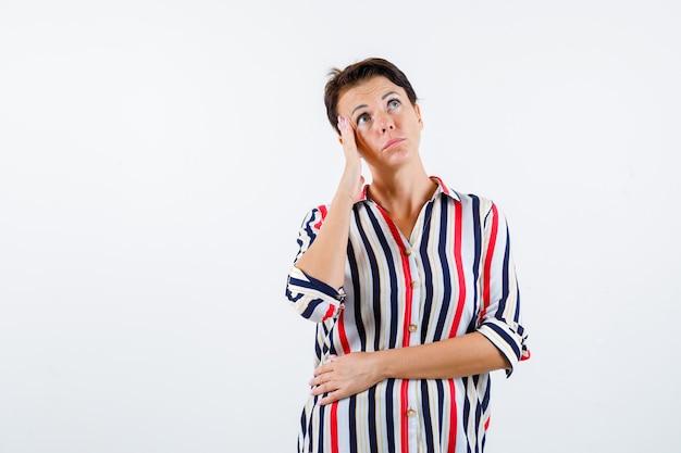 Donna matura in piedi nella posa di pensiero, appoggiando la guancia sul pam in camicetta a righe e guardando pensieroso. vista frontale.