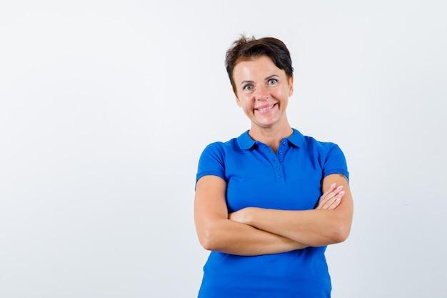 青いtシャツを着て腕を組んで立っている成熟した女性と自信を持って、正面図。