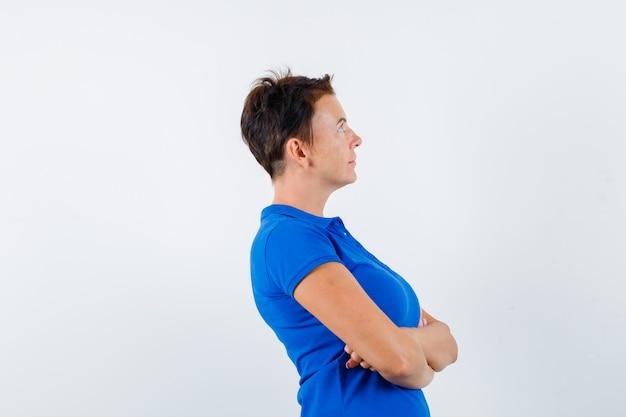 青いtシャツを着て腕を組んで立っていると物思いにふける成熟した女性。