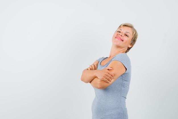 Зрелая женщина, стоящая со скрещенными руками в серой футболке и гордо выглядящая