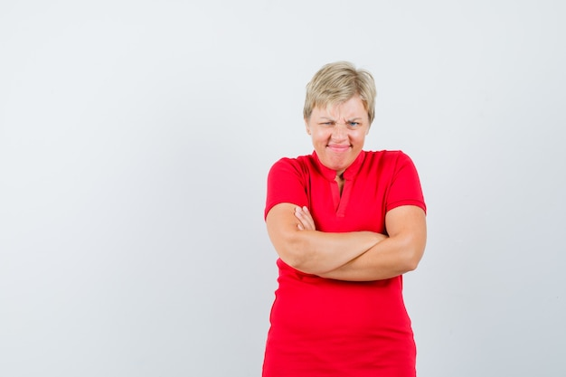 赤いtシャツを着て腕を組んで立っていると頑固に見える成熟した女性。