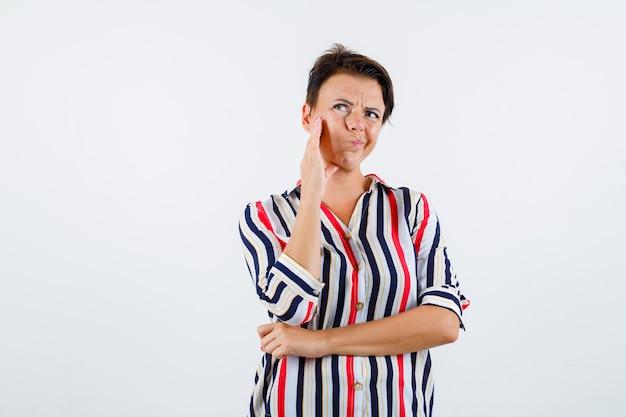 Donna matura in camicetta a righe che si appoggia sulla guancia sul palmo mentre pensa a qualcosa, tenendo la mano sulla vita e guardando pensieroso, vista frontale.