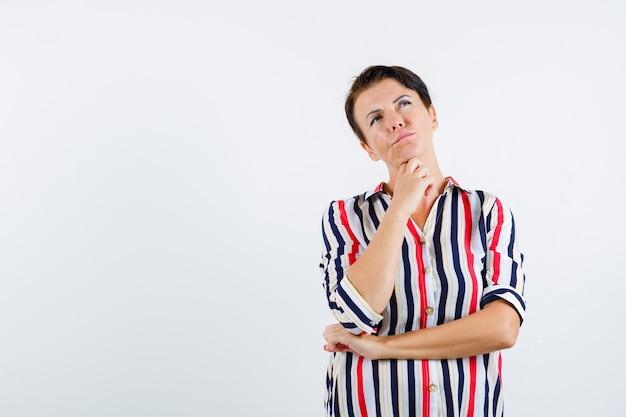 Donna matura in camicetta a righe con il mento appoggiato sulla mano, pensando a qualcosa e guardando pensieroso, vista frontale.