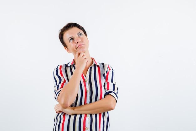 Donna matura in camicetta a righe con il mento appoggiato sul palmo, pensando a qualcosa e guardando pensieroso, vista frontale.