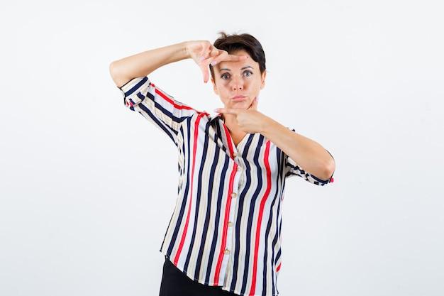 Donna matura in camicetta a righe che mostra il gesto del telaio, labbra curve e sguardo serio, vista frontale.