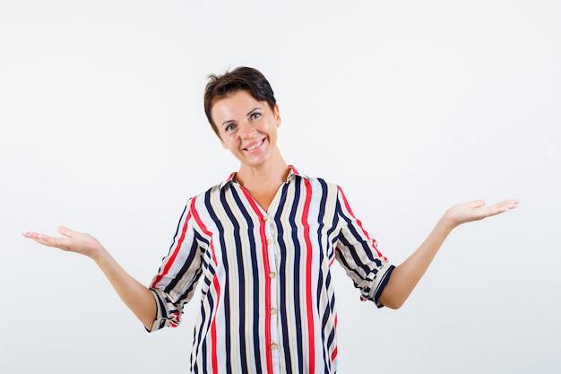 Donna matura in camicetta a righe che mostra gesto impotente e cerca vivace, vista frontale.