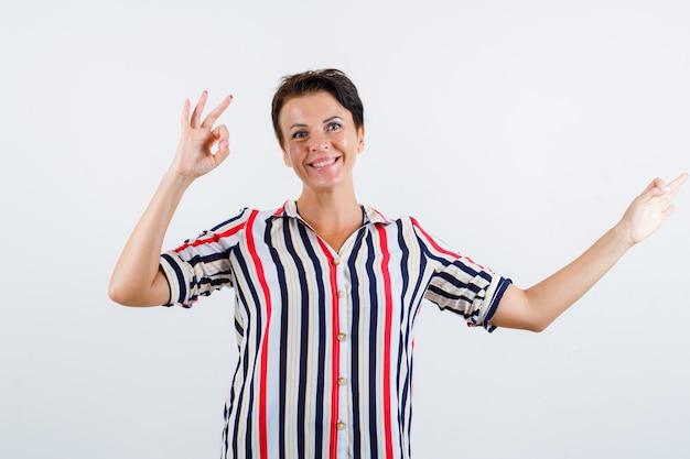 Donna matura in camicetta a strisce che mostra segni giusti e che sembra allegra, vista frontale.