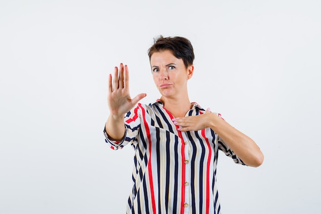 Mature woman in striped blouse showing stop sign, holding hand over chest and looking serious , front view.