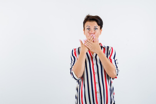 Mature woman in striped shirt holding hands on mouth and looking surprised , front view.