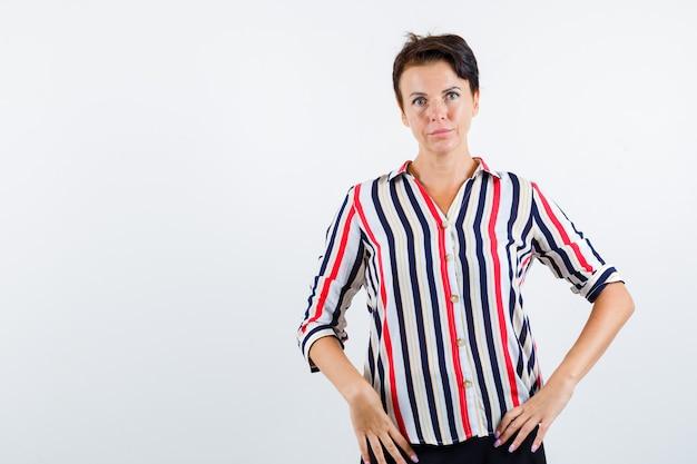 Donna matura in camicia a righe tenendo le mani sulla vita e guardando fiducioso, vista frontale.