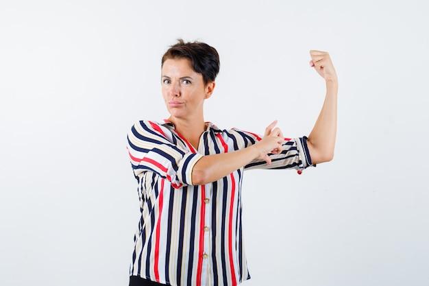 Donna matura in camicia a righe che mostra il gesto di potenza, misurando le dimensioni dei bicipiti e guardando fiducioso, vista frontale.