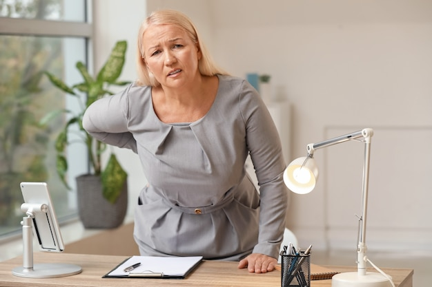 Mature woman suffering from back pain in office