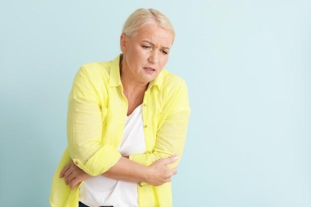 밝은 배경에 팔꿈치 통증으로 고통받는 성숙한 여성