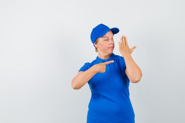 Donna matura in maglietta che indica al suo braccio alzato e che osserva concentrata