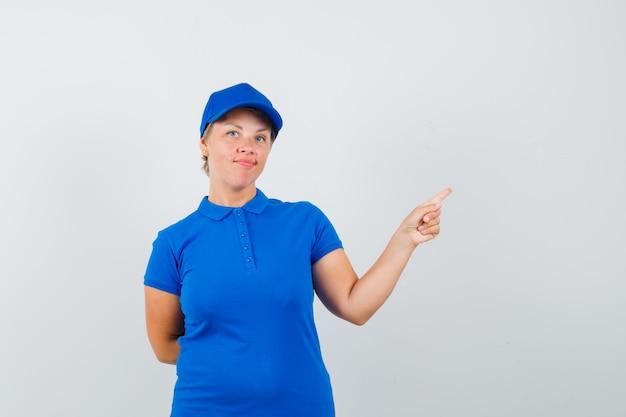 Donna matura in maglietta che punta all'angolo superiore destro e che sembra sicura