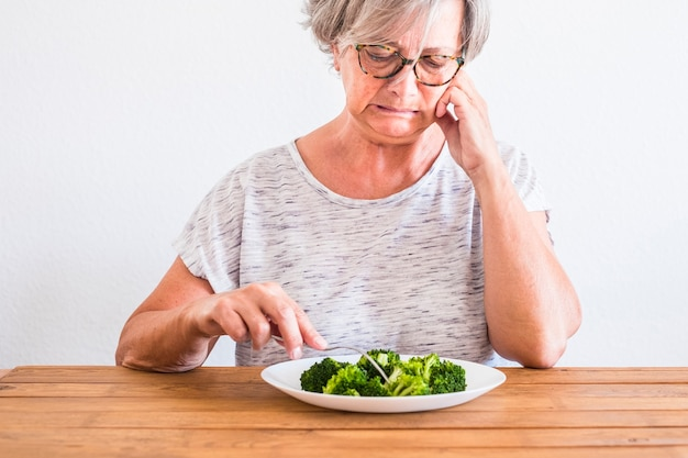 Mature woman at the table looking with disgustin face at healthy food or broccoli - touching the vegetable and dislike the diet lifestyle