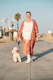 夏の日に犬と散歩をしている成熟した女性