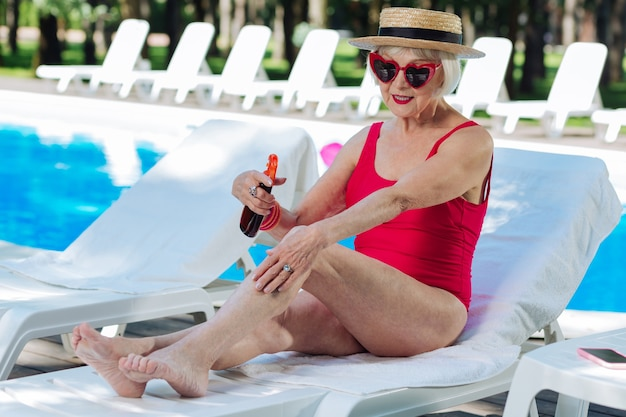 Mature woman taking care of her skin while using sun protection cream before sunbathing