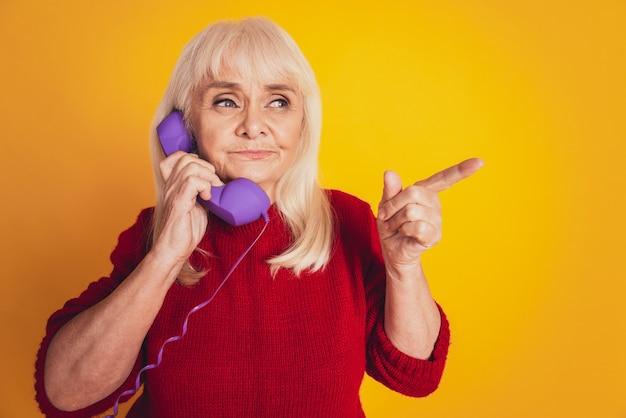 Зрелая женщина разговаривает по телефону указательным пальцем на пустом месте на желтом фоне