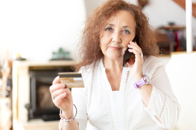 Mature woman talking on the phone from her home while holding a credit card in her hand.