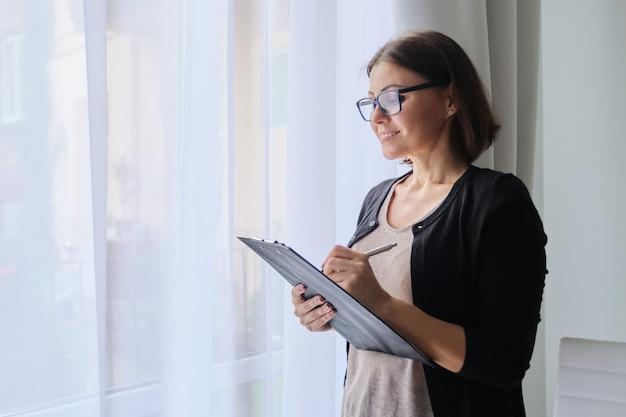 Зрелая женщина-учитель заметок, стоя у окна в офисе.