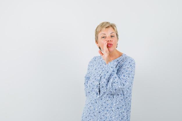 Зрелая женщина рассказывает секрет за рукой в рубашке