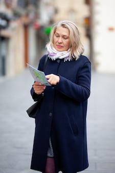 손에지도와 성숙한여 인 관광은 마을의 거리를 산책.