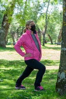 成熟した女性が音楽やポッドキャストを聴きながらストレッチをしている公園でトレーニング
