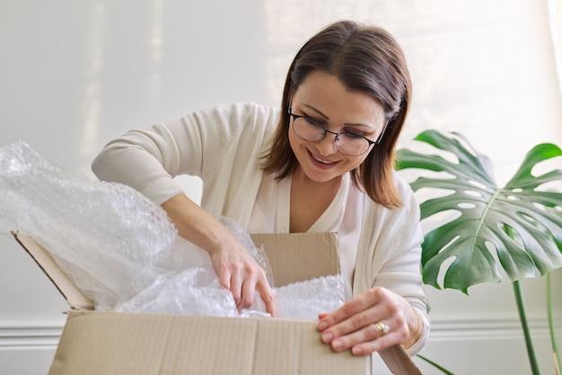 성숙한 여성은 집에서, 사무실에서 탁자 위에 골판지 상자의 포장을 풉니다. 국제 우편 배송, 상품 자동 배송, 화물 서비스. 여성은 온라인 상점에서 구매한 구매를 받았습니다.
