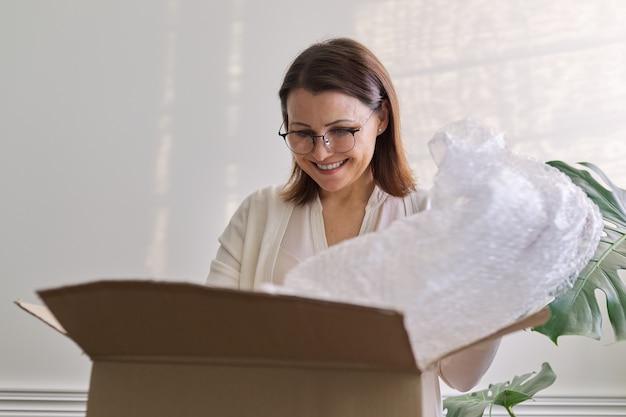 Зрелая женщина распаковывает картонную коробку на столе дома, в офисе. услуга по международной почтовой доставке, авто доставка товаров, грузов. женщины получили покупки, купленные в интернет-магазинах